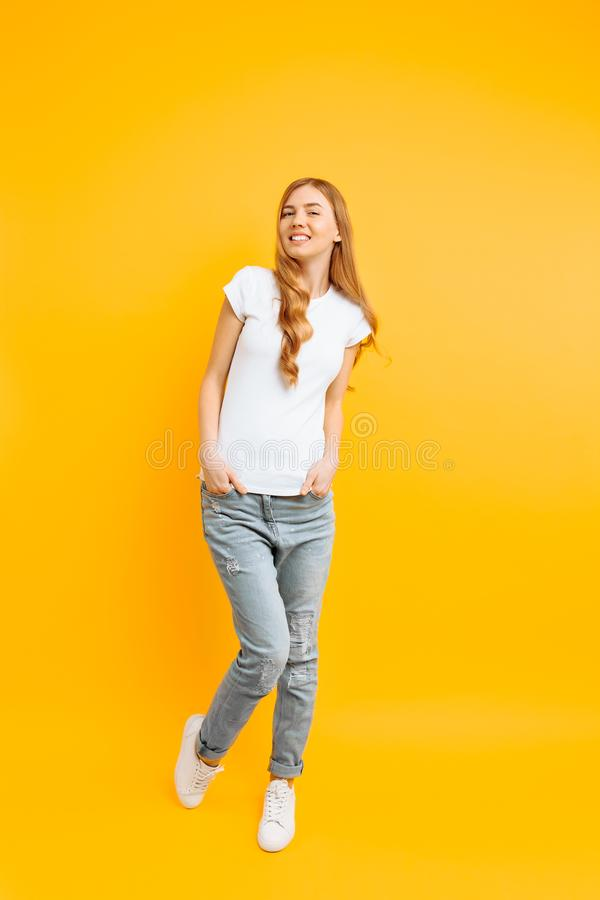 Full length portrait of a cheerful beautiful girl, posing on a yellow background royalty free stock photo