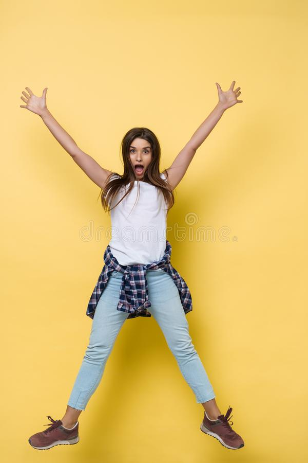 Full length portrait of a cheerful casual caucasian woman jumping isolated over yellow background stock image