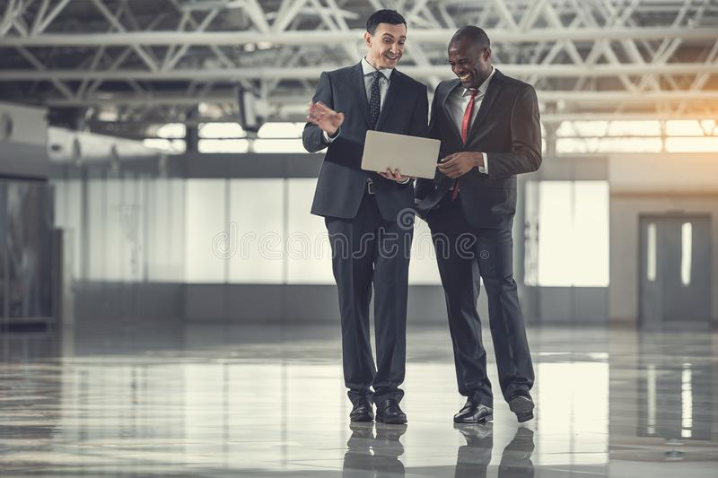 Happy male workers having job with laptop royalty free stock images