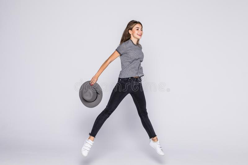 Full length portrait of a cheerful cute woman jumping with hat isolated on a white background. Full length portrait of a cheerful cute woman jumping isolated on stock photo