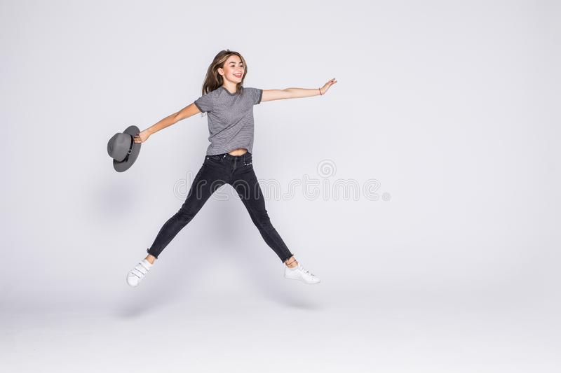 Full length portrait of a cheerful cute woman jumping with hat isolated on a white background stock photo
