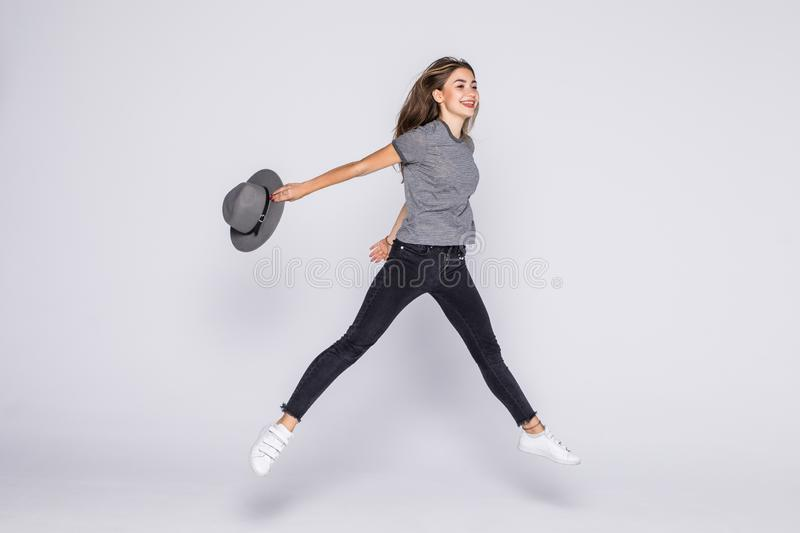 Full length portrait of a cheerful cute woman jumping with hat  on a white background. Full length portrait of a cheerful cute woman jumping  on a white royalty free stock photo
