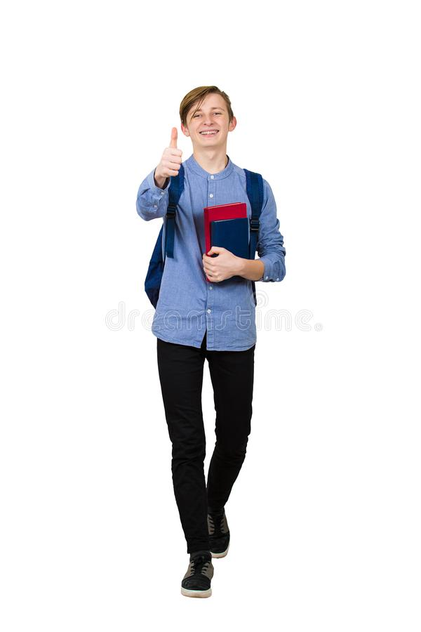 Full length portrait of cheerful student boy going to school holding two books and showing thumb up gesture. Joyful teen walking royalty free stock photography
