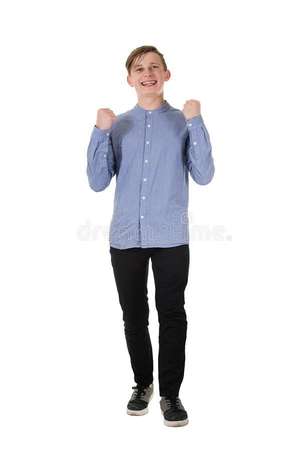 Full length portrait of a cheerful teenage boy raising his hands up, holding fists, like a winner celebrating success and victory royalty free stock photography