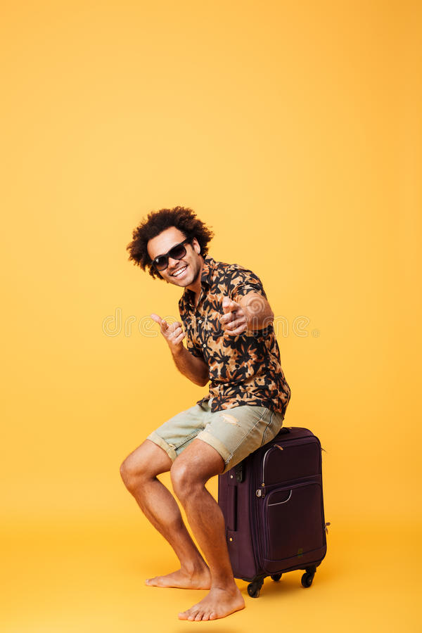 Full length portrait of a cheerful young african tourist guy royalty free stock photo