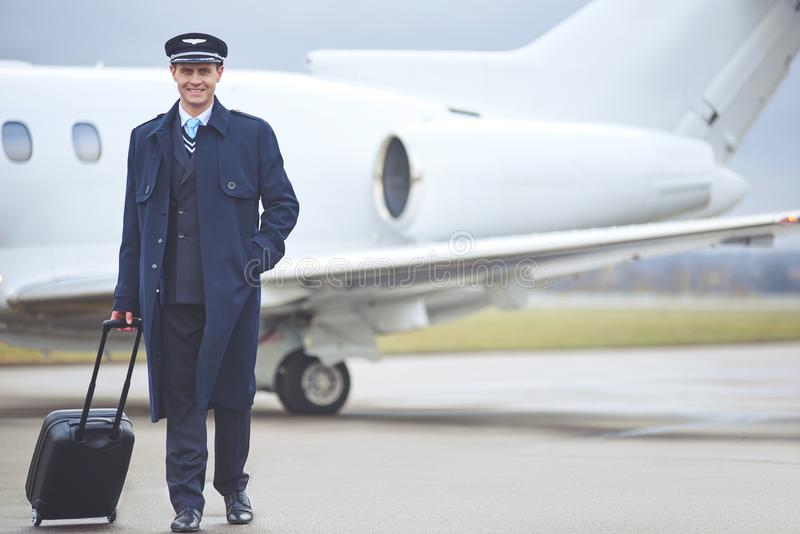 Outgoing pilot holding baggage in arm royalty free stock photo