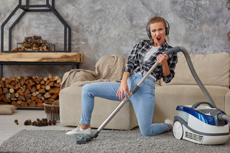 Full length portrait of cheerful young woman 20s listening to music via headphones and having fun with vacuum cleaner in royalty free stock images