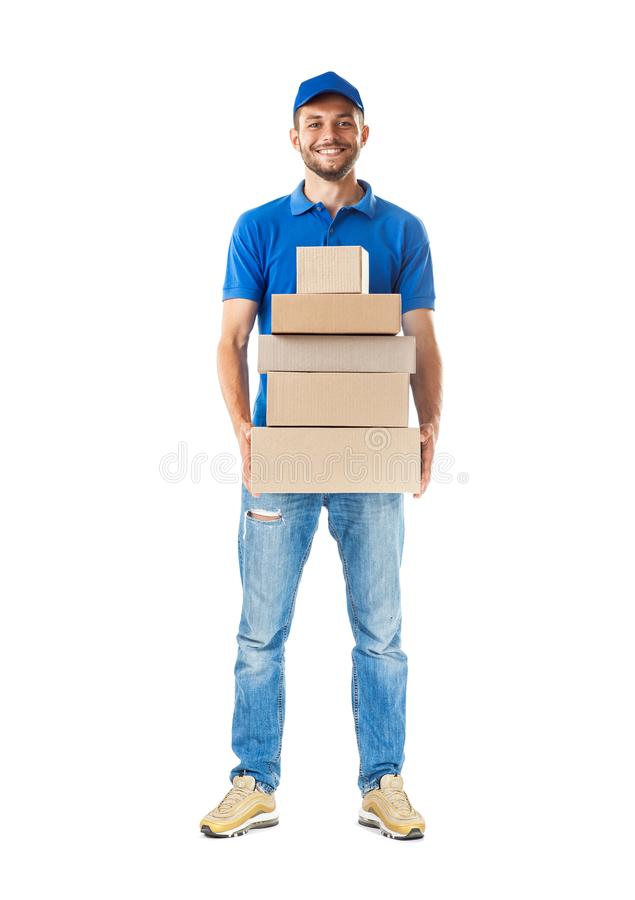 Full length portrait of confidence express courier holding pile. Of cardboard boxes isolated on white background royalty free stock images