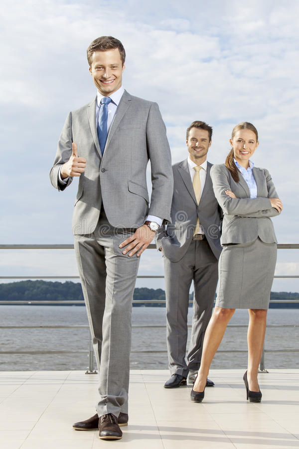 Full length portrait of confident businessman gesturing thumbs up while standing with coworkers on terrace against sky royalty free stock photos