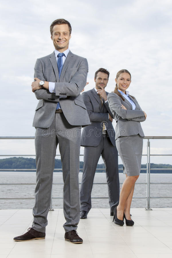 Full length portrait of confident businessman standing with coworkers on terrace against sky stock images