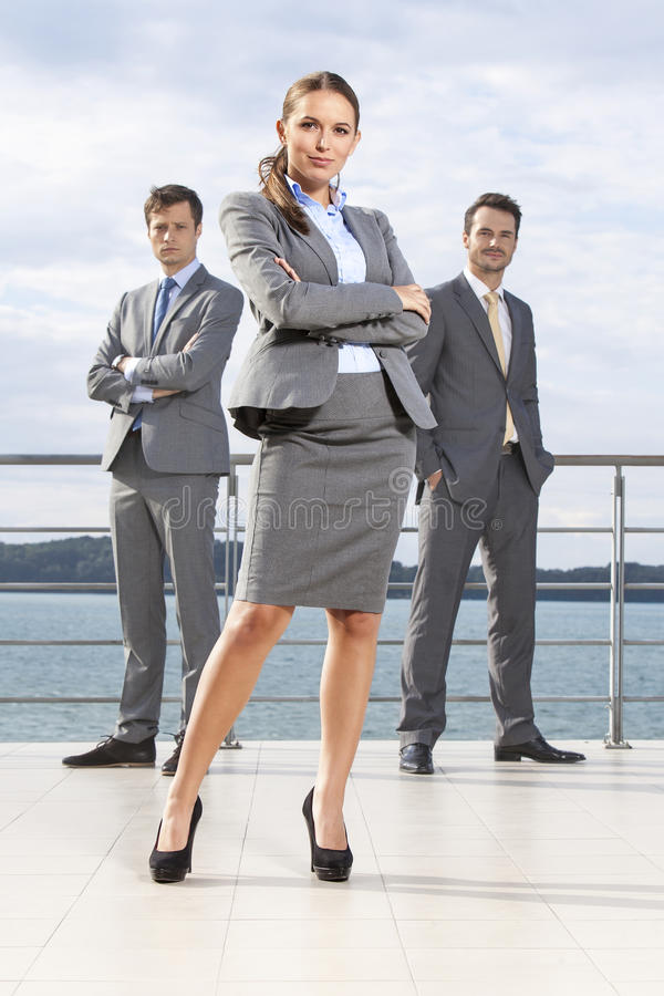 Full length portrait of confident businesswoman standing with coworkers on terrace against sky royalty free stock images