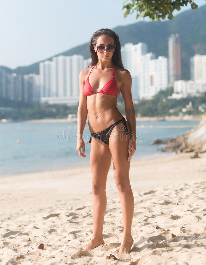 Full-length portrait of confident fitness female model wearing swimsuit standing on sandy beach with high buildings in stock image