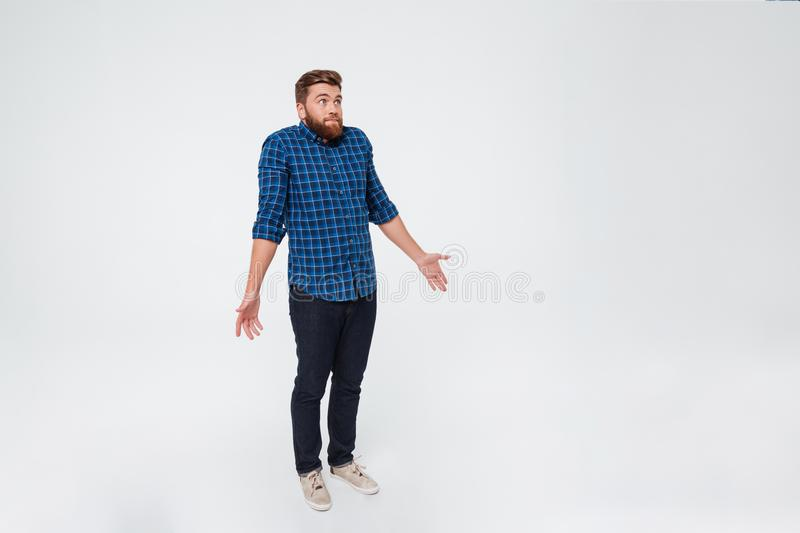 Full length portrait of a confused young bearded man. Standing and shrugging shoulders over white background royalty free stock images