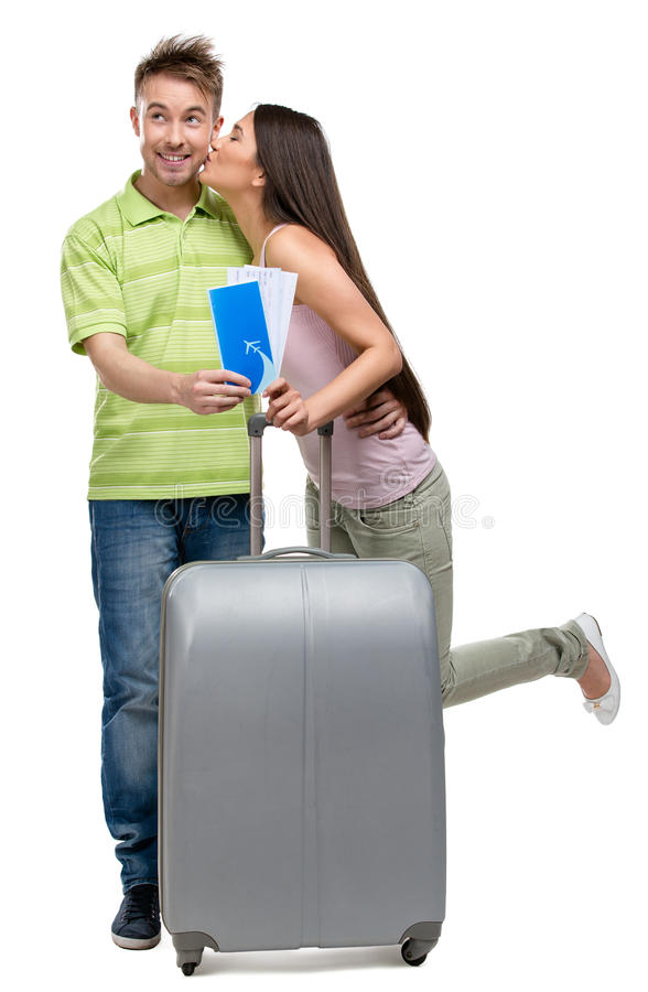 Full-length portrait of couple with suitcase and tickets. Full-length portrait of embracing couple with suitcase and tickets, isolated on white. Concept of stock photography
