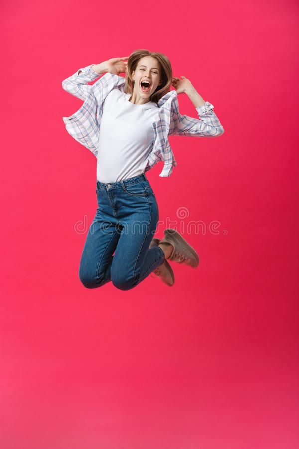 Full length portrait of a crazy joyful girl in casual cloth while jumping isolated over pink background stock photos