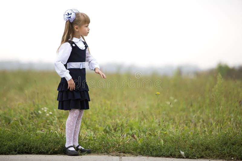 Full-length portrait of cute adorable serious thoughtful first grader girl in school uniform and white bows in long blond hair on royalty free stock photography