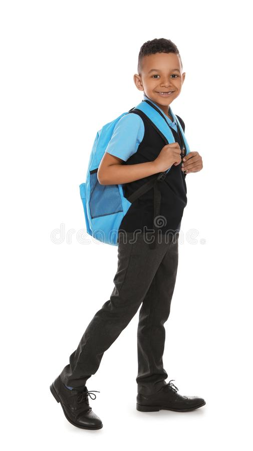 Full length portrait of cute African-American boy in school uniform with backpack on white stock photos