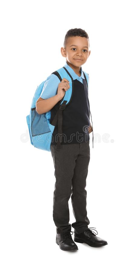 Full length portrait of cute African-American boy in school uniform with backpack on white stock photo