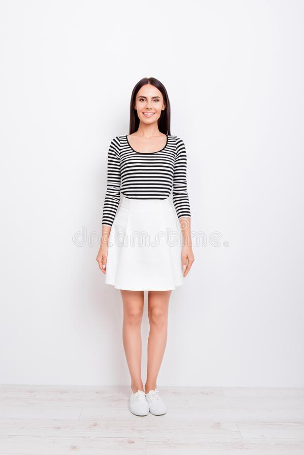 Full length portrait of cute brunette lady. She is wearing casual outfit and stands on pure white background royalty free stock photo