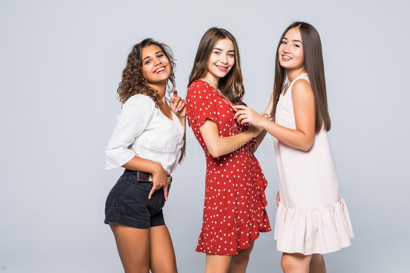 Full-length portrait of cute girls internatonal friends in casual clothes standing in studio with white background royalty free stock image