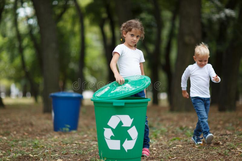 A little girl putting a bucket lid on a green recycling bin on a blurred natural background. Ecology and children. stock image