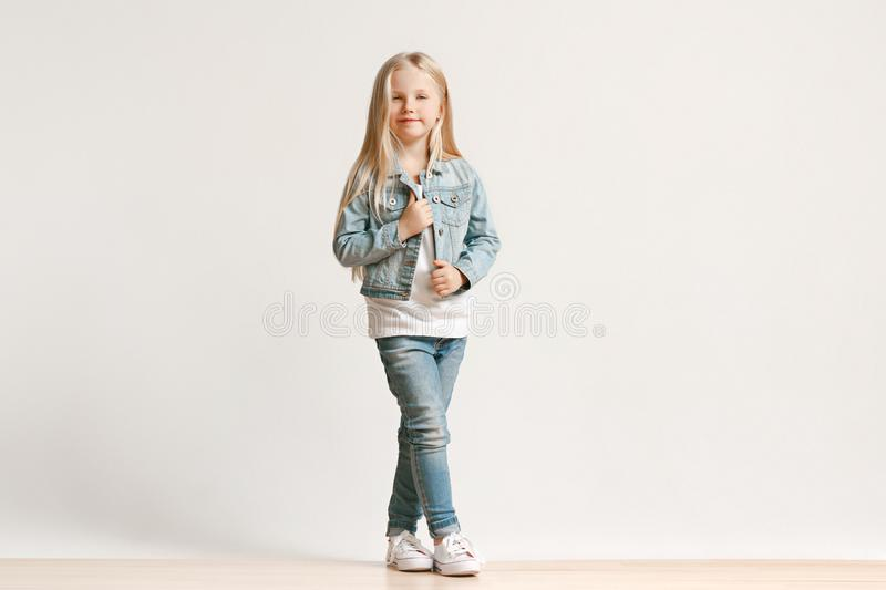 Full length portrait of cute little kid in stylish jeans clothes looking at camera and smiling royalty free stock photo