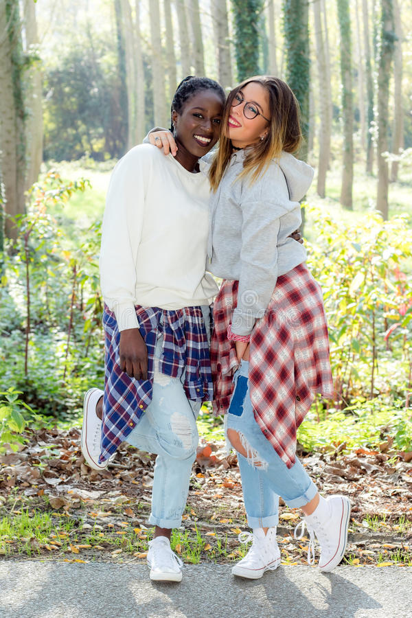 Full length portrait of diverse teen girls in woods. royalty free stock photos