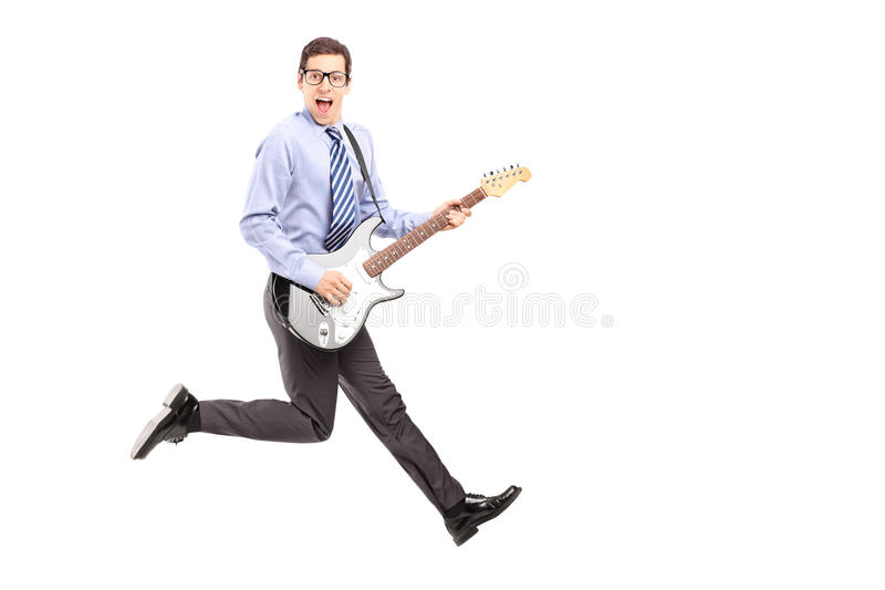 Full length portrait of energetic young male jumping with a guitar. Isolated on white background stock photo