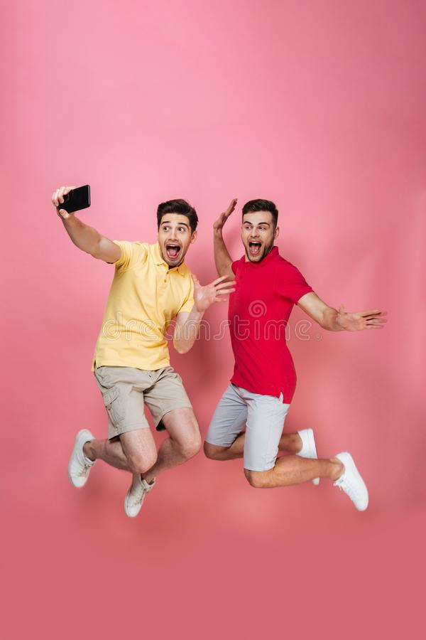 Full length portrait of an excited gay male couple royalty free stock photo