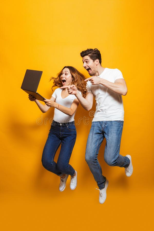 Full length portrait of excited man and woman jumping and using. Full length portrait of excited men and women jumping and using black laptop isolated over royalty free stock photography
