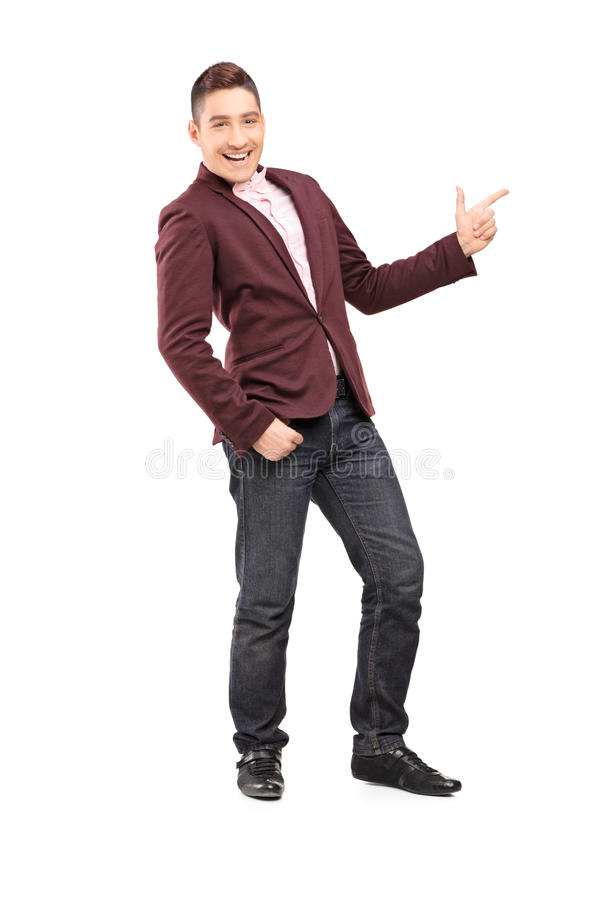 Full length portrait of a fashionable smiling guy pointing with. Hand isolated on white background royalty free stock photos