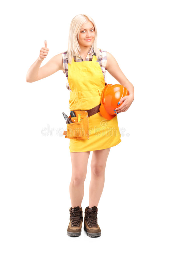 Full length portrait of a female construction worker with equipment giving thumb up royalty free stock images