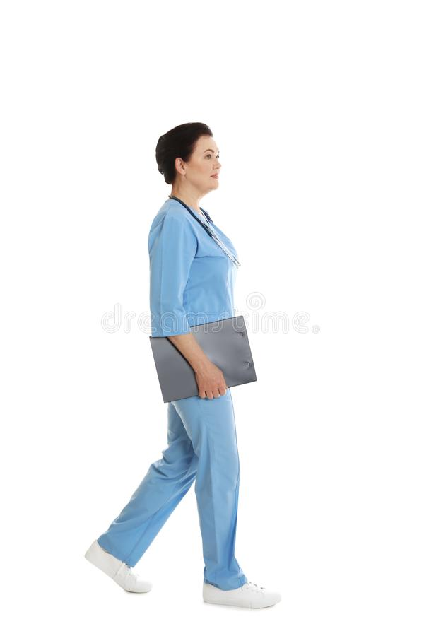 Full length portrait of female doctor in scrubs with clipboard on white. Medical staff. Full length portrait of female doctor in scrubs with clipboard isolated stock image