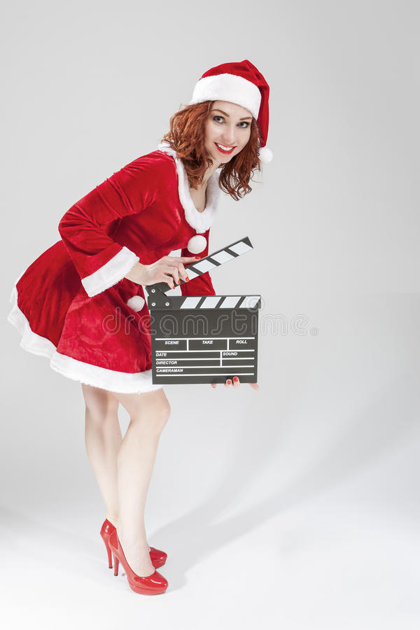 Full Length Portrait of Female Santa Helper Holding Clapperboard. In Front Ready to Set off Filming. Against White Background. Vertical Image Composition royalty free stock photos