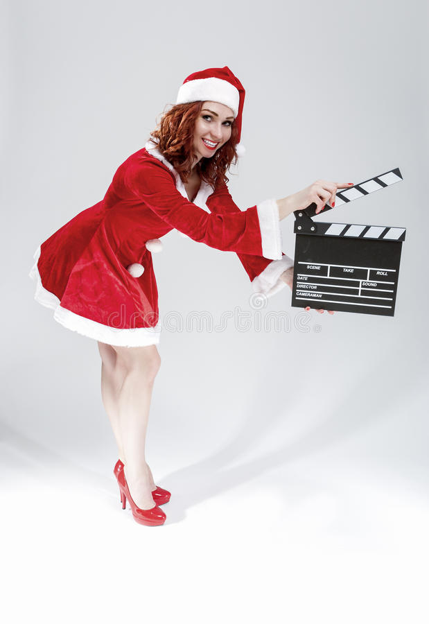 Full Length Portrait of Female Santa Helper Holding Clapperboard. In Front Ready to Set off Filming. Against White Background. Vertical Image Composition royalty free stock photography