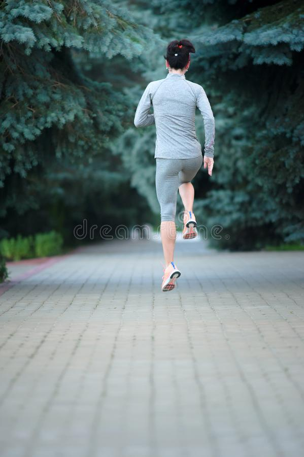 Full length portrait of a fitness woman running at the park. Back view training athlete stock photo