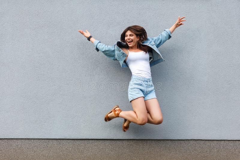 Full length portrait of free happy beautiful woman in casual jeans denim style in summertime jumping at light blue wall, having stock image