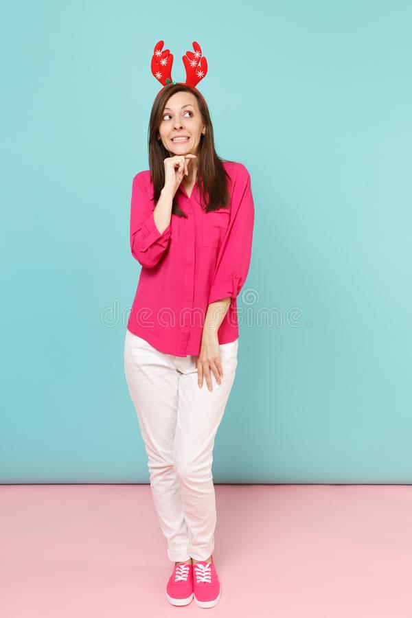 Full length portrait of fun young woman in rose shirt blouse, white pants, deer horns posing isolated on bright pink. Blue pastel wall background studio stock image