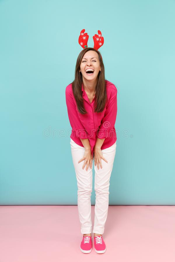 Full length portrait of fun young woman in rose shirt blouse, white pants, deer horns posing isolated on bright pink. Blue pastel wall background studio royalty free stock photos
