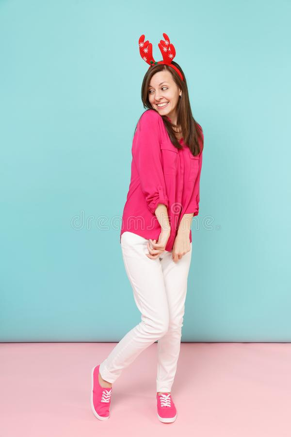 Full length portrait of fun young woman in rose shirt blouse, white pants, deer horns posing isolated on bright pink. Blue pastel wall background studio royalty free stock images
