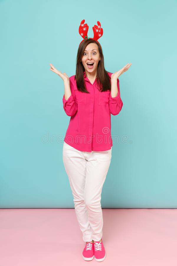 Full length portrait of fun young woman in rose shirt blouse, white pants, deer horns posing isolated on bright pink. Blue pastel wall background studio royalty free stock image