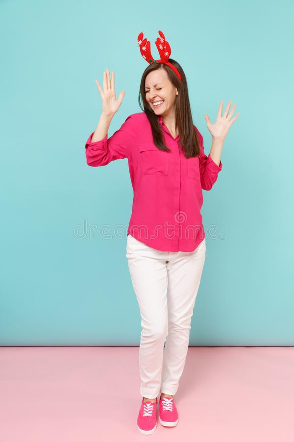 Full length portrait of fun young woman in rose shirt blouse, white pants, deer horns posing isolated on bright pink. Blue pastel wall background studio stock photography