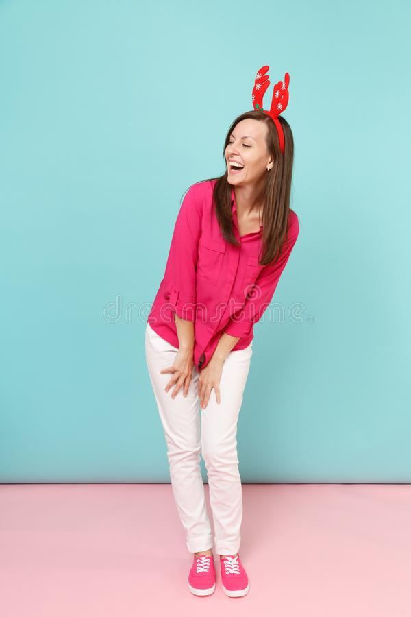Full length portrait of fun young woman in rose shirt blouse, white pants, deer horns posing isolated on bright pink. Blue pastel wall background studio royalty free stock photo