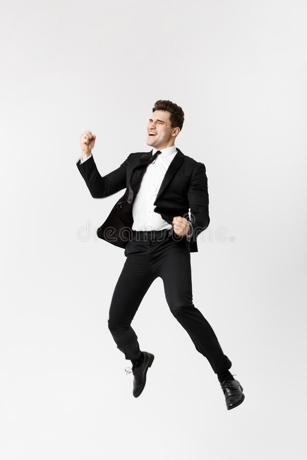 Full length Portrait Funny cheerful businessman jumping in air over gray background royalty free stock image