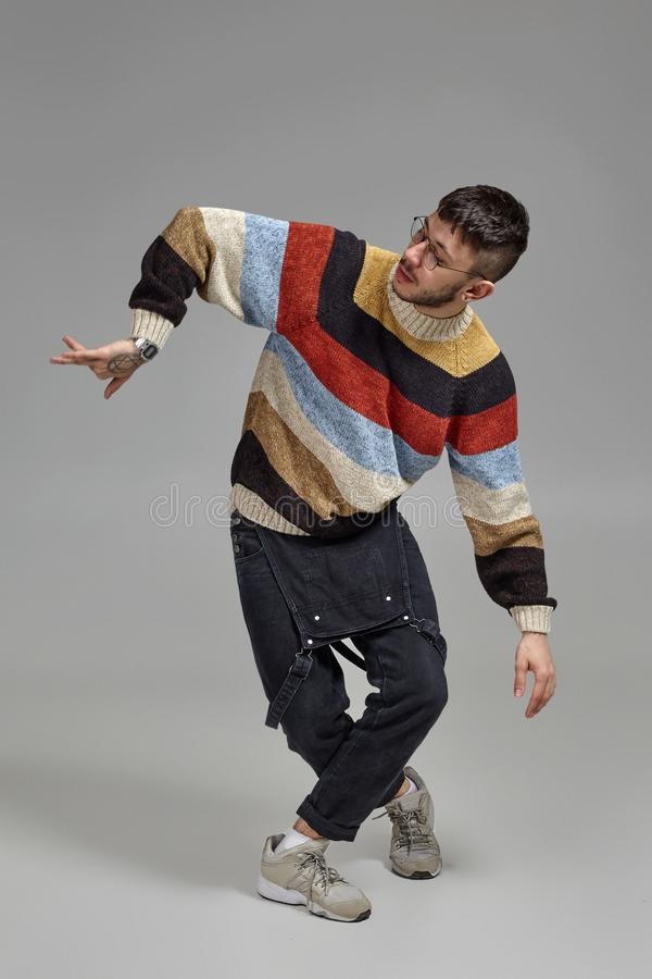 Full-length portrait of a funny guy dancing in studio on a gray background. stock photos