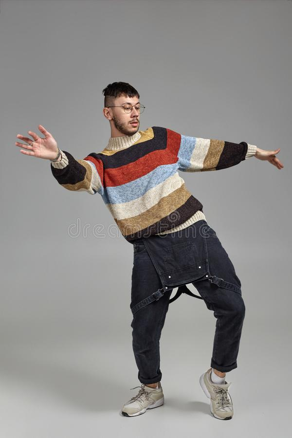 Full-length portrait of a funny guy dancing in studio on a gray background. stock photo