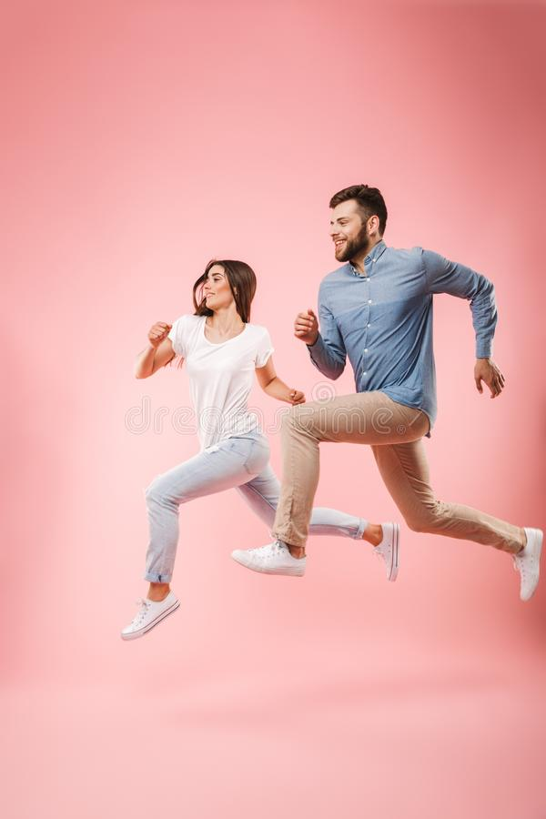 Full length portrait of a funny young couple running fast royalty free stock photo