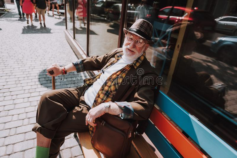 Fashionable old man spending time in the city. Full length portrait of good looking smiling senior male resting on colorful bench and holding stick stock photos