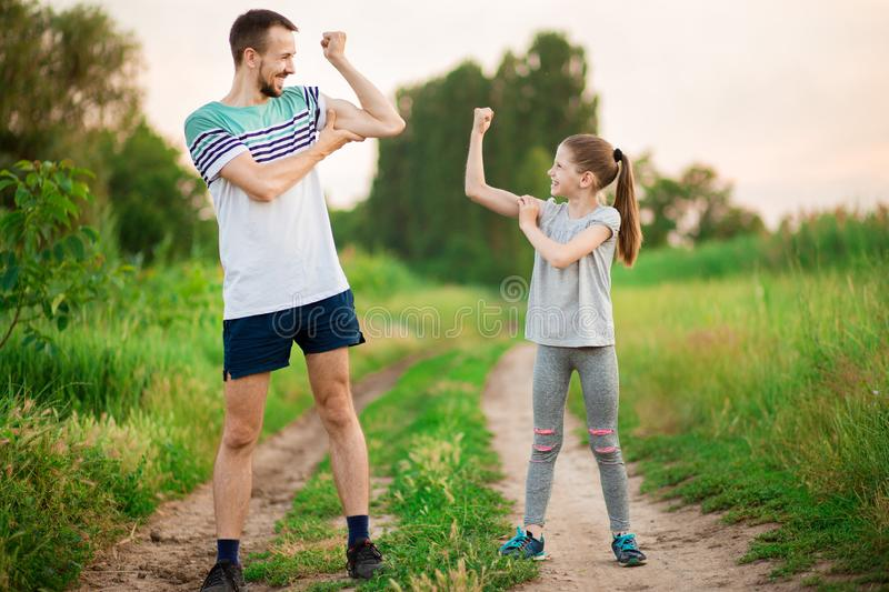 Full length portrait of handsome father and little daughter showing their muscles, looking at camera and smiling outdoor royalty free stock photos