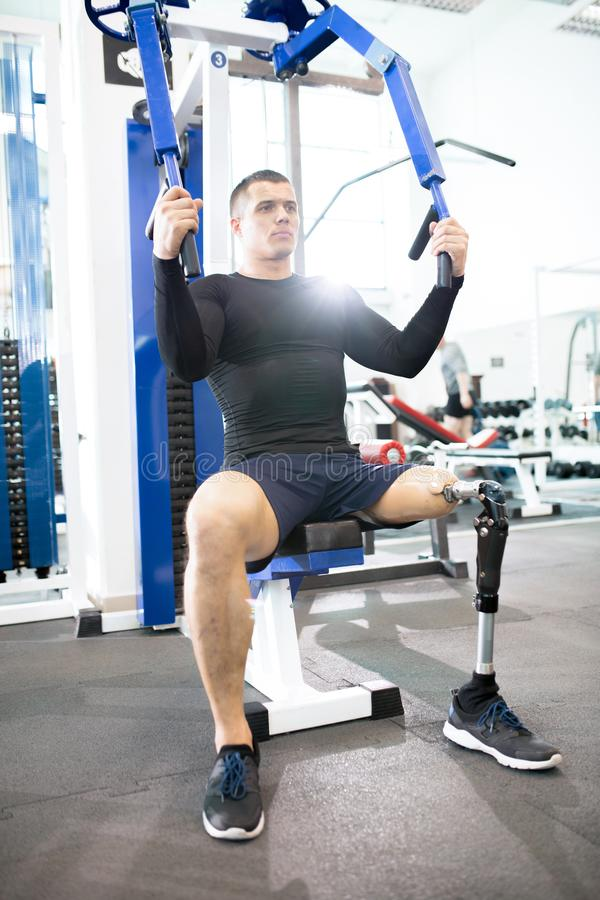 Adaptive Athlete Using Exercise Machines in Modern Gym royalty free stock images